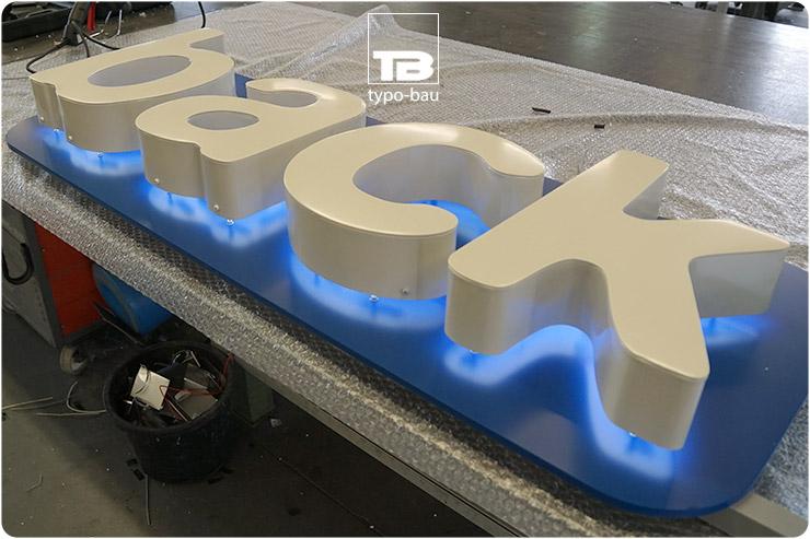 Leuchtbuchstaben ausgeführt im Profil 3, vormontiert auf einer Werbeblende, Indirekt leuchtend.