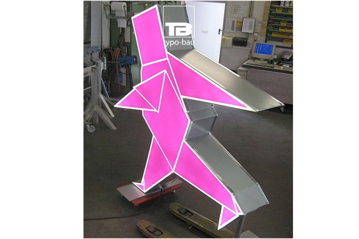 Formgebautes Leuchttransparent mit LED Ausleuchtung als Standfigur für einen Messestand.